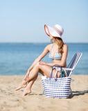 晒日光浴在海滩睡椅的女孩 库存图片