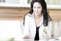 使用她的膝上型计算机的妇女在厨房 免版税库存图片