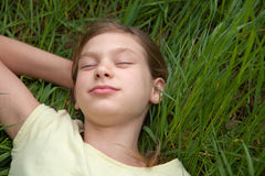 说谎在一个绿色草甸的孩子 免版税图库摄影
