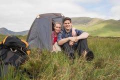 在远足以后结合坐在他们的帐篷和微笑对照相机 图库摄影