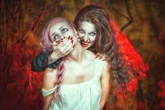 万圣夜吸血鬼和她的受害者 库存图片