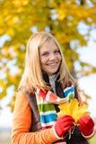 微笑的白肤金发的青少年的女孩秋天森林叶子 免版税库存图片
