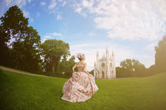葡萄酒礼服的公主在不可思议的城堡前 免版税库存照片