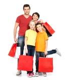 与站立在演播室的购物袋的家庭 免版税库存照片