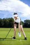 打在草的俏丽的女孩高尔夫球 免版税库存图片