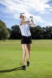 打在草的女孩高尔夫球 图库摄影