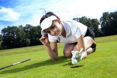 打在草的俏丽的女孩高尔夫球 免版税库存照片
