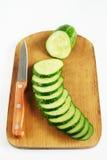 成熟新鲜的黄瓜和刀子在切板 免版税库存照片