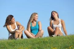 谈话小组三个少年的女孩笑和室外 免版税库存照片