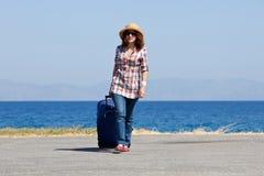 Привлекательная женщина с чемоданом на пляже Стоковые Фото