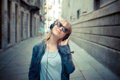 听到音乐的美丽的白肤金发的妇女 库存照片