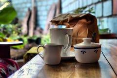 咖啡具和纸组装在桌上 免版税库存照片