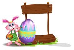 兔宝宝绘画和一块空的牌 免版税库存图片