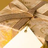 Χρυσό χριστουγεννιάτικο δώρο με την κενή ετικέττα που επιθυμεί την κάρτα Στοκ εικόνα με δικαίωμα ελεύθερης χρήσης