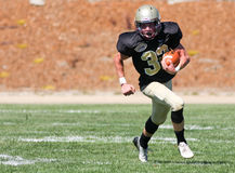 Футболист средней школы бежать с шариком во время игры Стоковое Изображение RF