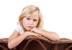 坐在椅子的哀伤的女孩 免版税库存照片