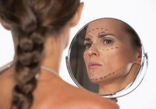 有整容手术标记的妇女在看在镜子的面孔 免版税库存图片