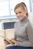 有片剂计算机的微笑的妇女 图库摄影