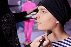 化妆在射击他前的年轻演员在夹子 免版税库存照片