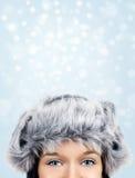 在多雪的背景的俏丽的眼睛 免版税库存照片