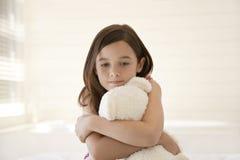 拥抱玩具熊的哀伤的女孩 库存照片