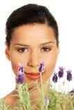 美丽的女孩气味淡紫色花 免版税图库摄影