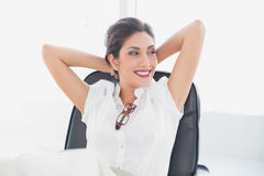 坐在她书桌微笑的斜倚的女实业家 库存照片