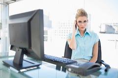 严厉的有女实业家佩带的玻璃电话 免版税库存图片