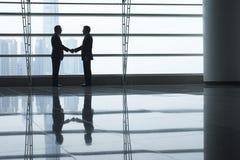 握手的商人在机场终端 免版税库存照片