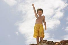 有手被上升的身分的小男孩在岩石 免版税库存照片