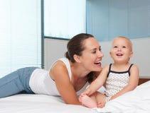 笑与逗人喜爱的婴孩的美丽的母亲在床上 图库摄影