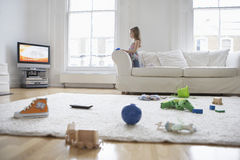 看与玩具的女孩电视在地板上 免版税库存照片