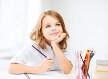 与铅笔的女孩图画在学校 免版税库存图片