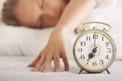 年轻睡觉的妇女和闹钟在床上 免版税图库摄影
