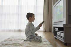 在电视的男孩观看的动画片 库存照片