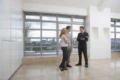 显示夫妇新的公寓的房地产开发商 免版税库存照片
