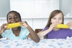 吃玉米棒子的不同种族的女孩 免版税库存照片
