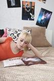 十几岁的女孩在床上的看杂志 库存照片