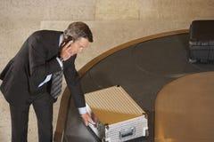 在行李转盘的商人要求的手提箱在机场 免版税库存照片