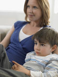 在家看电视的男孩和母亲 免版税库存图片