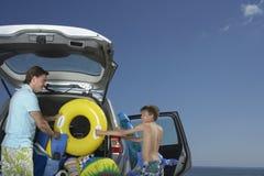 卸载汽车的父亲和儿子在海滩 免版税库存图片