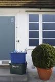 回收容器和盆的植物在大厦之外 免版税库存照片