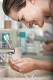 妇女洗涤的面孔在卫生间里 免版税库存图片