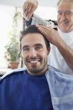 得到理发的人从美发师 免版税图库摄影
