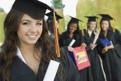 有文凭的学生,当站立在背景中的朋友在大学时 免版税库存照片