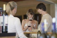 愉快的夫妇品尝酒 免版税库存照片