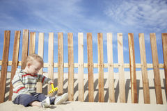使用与在海滩的玩具犁耙的男婴 图库摄影