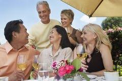 享受饮料的朋友在饭桌上 免版税库存照片