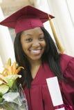 有证明的女学生和花束在毕业典礼举行日 免版税图库摄影