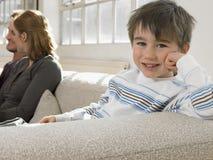 在家放松在有父母的沙发的愉快的男孩 免版税库存照片